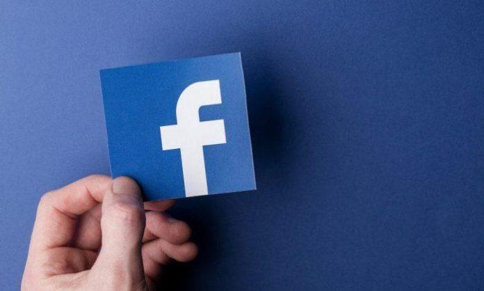 A hand holding a facebook logo