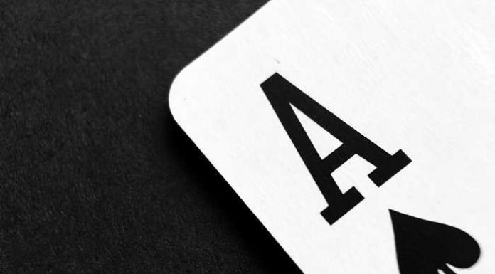 ace poker card on black table