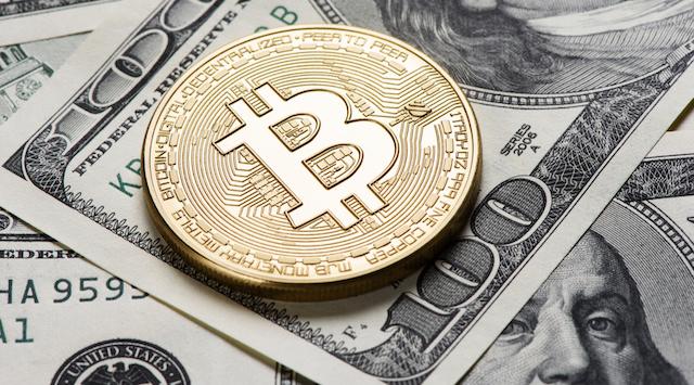 bitcoin on top of 100 dollar bills