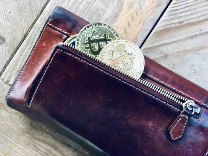 a wallet filled with physical bitcoin
