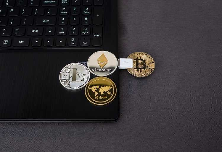 A laptop with replica coins of Litecoin, Ripple, ethereum and Bitcoin on it.