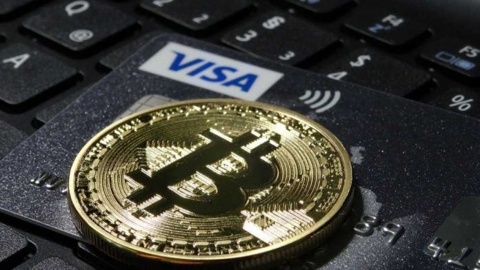 a physical bitcoin on top of a visa card
