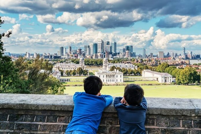two kids watching over the wall the bit town