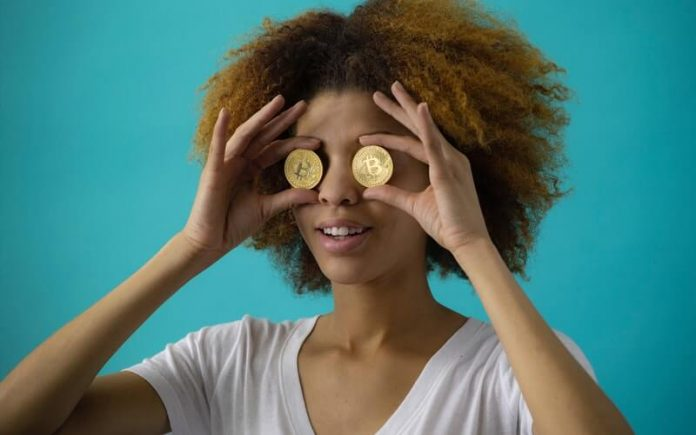 woman holding two bitcoin on her eyes